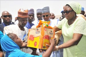 M.D. Dangote Foundation, Zouera Youssoufou, (Right) Presenting Food Items to one of The Beneficiary with his Farther (Left) While Borno State Governor (Middle) Alhaji Kashim Shettima, At The Distribution of  Dangote Foundation Donate Foods Items for Ramadan to (IDP) Internal Displays People  of Bakkasi Camp in Maiduguri Borno State. on 13-06-2016
